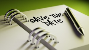 Closeup of a personal agenda setting an important date writing with pen. The words Save the date written on a white notebook to remind you an important appointment.